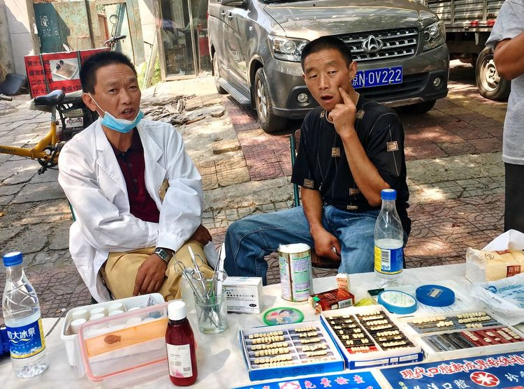 Sitting Two People Adult Outdoors Day Portrait People Young Adult Adults Only Supermarket Dentist Dentistry Tooth Chinese Market China China Photos Streetphotography Ambulance Service Medicine Pain Connected By Travel Stories From The City