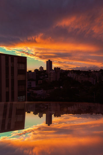 Sky Cloud - Sky Sunset Building Exterior Architecture Reflection Built Structure City Building Water Cityscape Nature Orange Color No People Dramatic Sky Outdoors Waterfront Office Building Exterior City Life Skyscraper Apartment