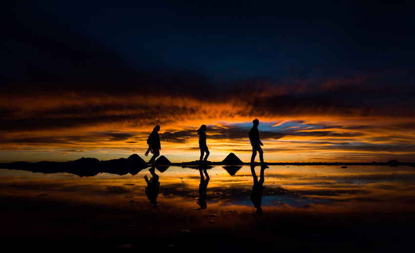 Tourists pose for pictures during sunset at Salar de Uyuni in Bolivia November 12, 2015. Bolivia Cloud Cloud - Sky Dramatic Sky Idyllic Nature Orange Sunset Salar De Uyuni Scenics Sky Sun Sunset Tranquility Water