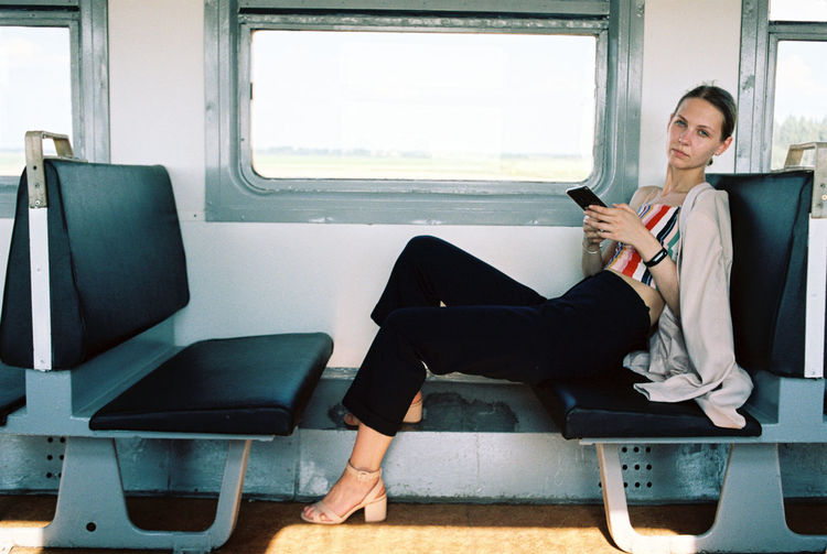 Portrait of woman using phone sitting in train