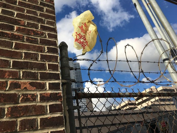 Low angle view of plastic bag stuck on razor wire fence