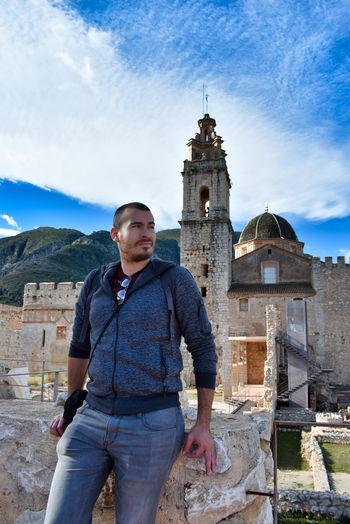 Portrait of man standing against historic building