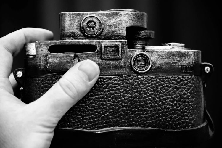 Close-up of cropped hand holding camera