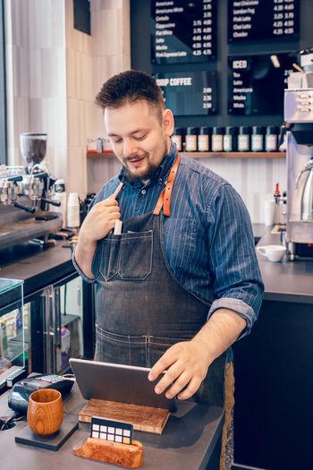 Young man preparing food at cafe