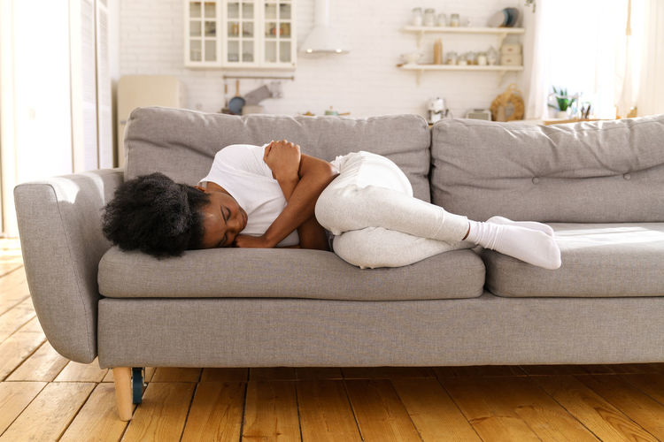 Young woman lying on sofa at home