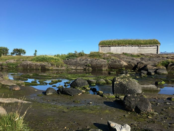 Grass Covered Hut On Rocks Against Clear Sky