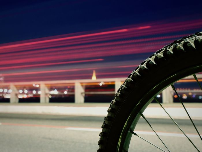 Close-up of bicycle tire by illuminated light trails on bridge at night
