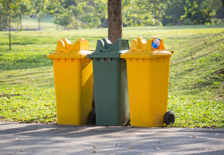 Yellow garbage can in park