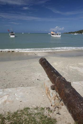Rusty canon at beach against sky