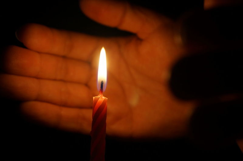 Human Hand Covering A Burning Candle