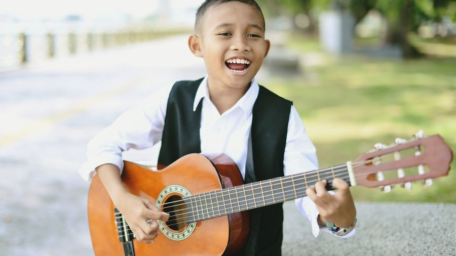 Close-up of boy playing guitar while standing at park