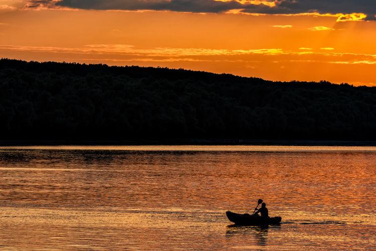 Silhouette people in boat on lake against orange sky