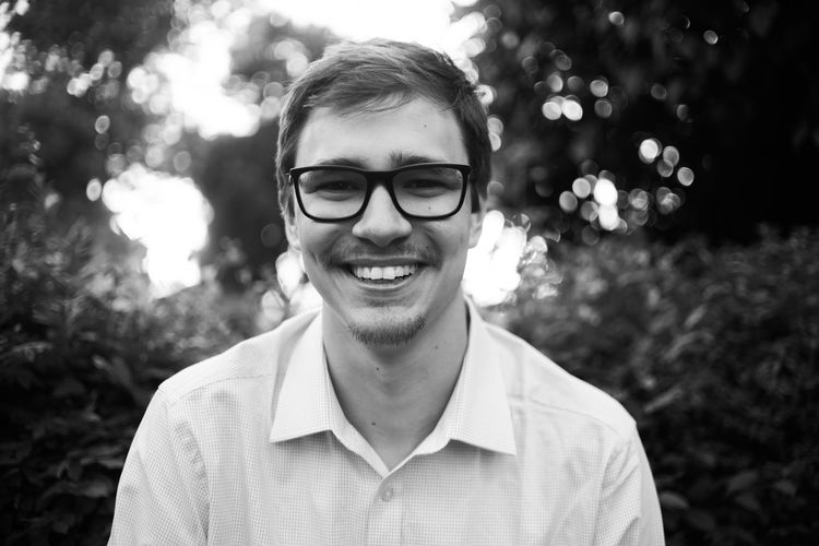 Portrait of smiling young man wearing eyeglasses outdoors