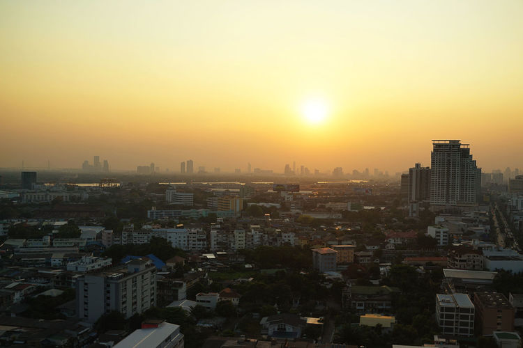 Bangkok city during sunset Architecture Building Building Exterior Built Structure City Cityscape Crowd Crowded High Angle View Nature Office Building Exterior Orange Color Outdoors Residential District Sky Skyscraper Smog Sun Sunlight Sunset