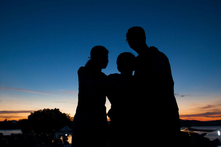 Silhouette family standing against sky during sunset