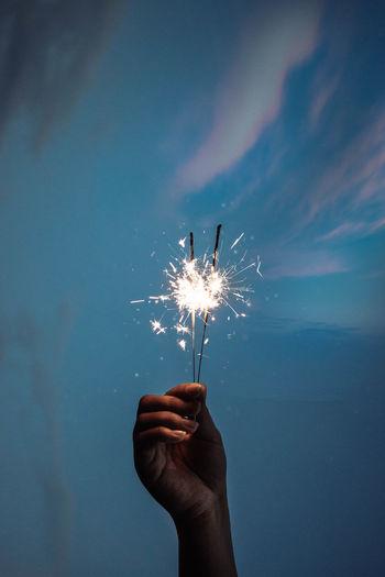 Cropped hand holding sparkler