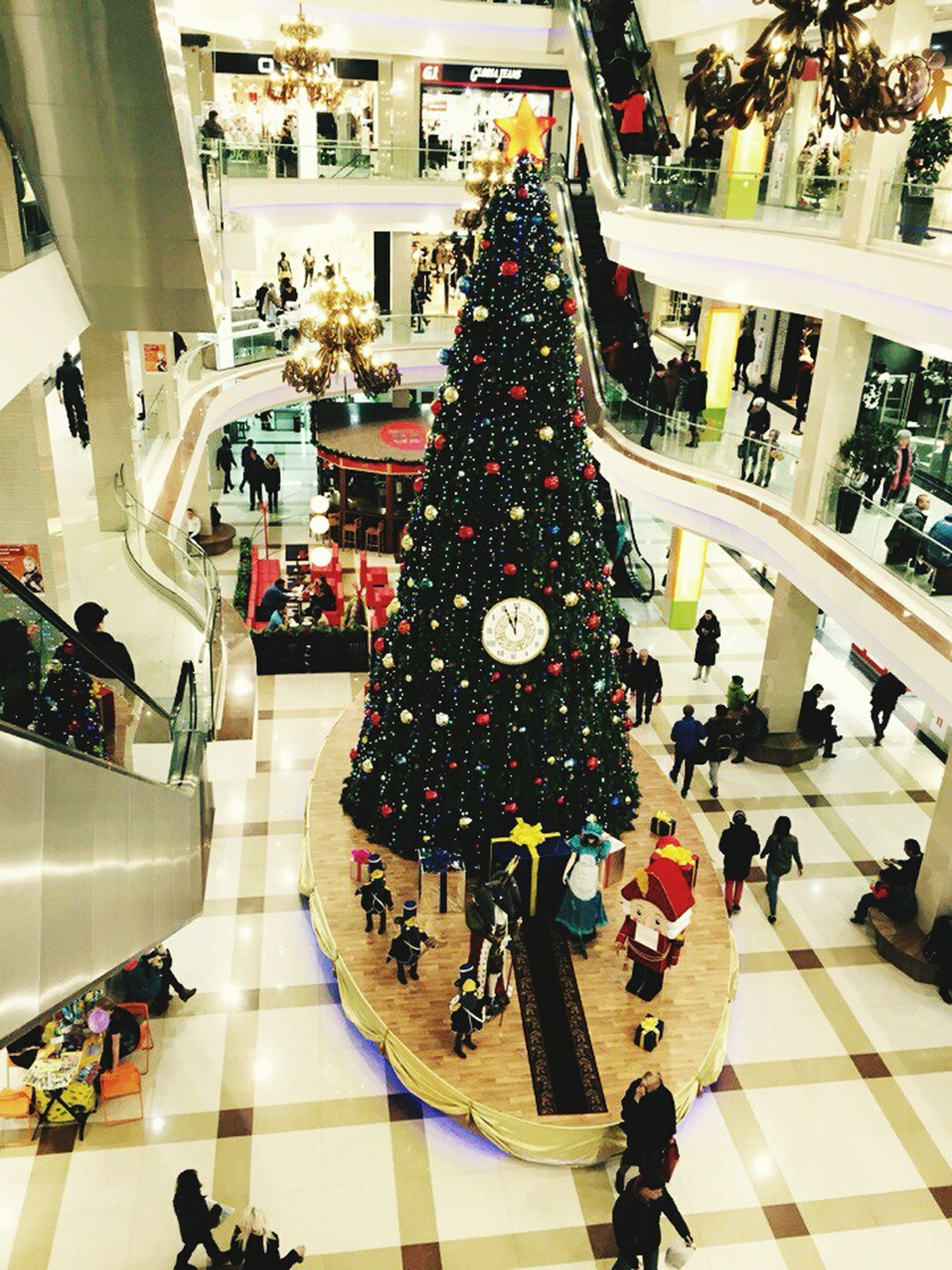 large group of people, shopping mall, escalator, christmas, store, real people, illuminated, christmas tree, indoors, people, adults only, day