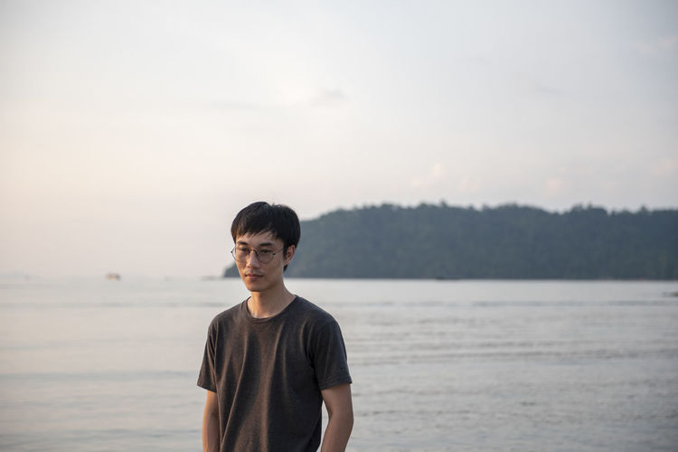 Young man standing in sea against sky during sunset