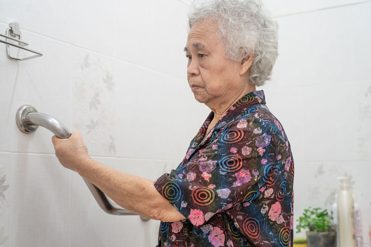 Senior woman holding handrail while standing by tiled floor in bathroom