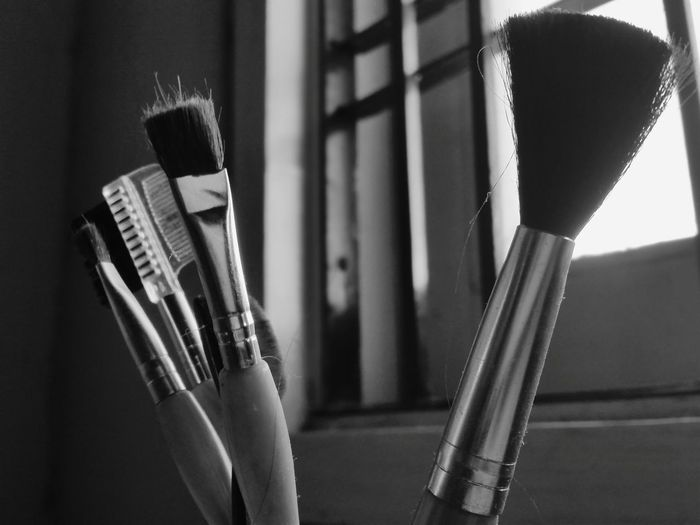 Close-Up Of Make-Up Brushes Against Window