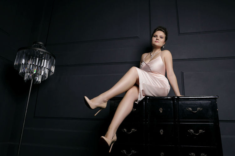 girl sitting on a furniture Beautiful Woman Beauty Dark Background Day Elégance Fashion Fashion Model Full Length Furniture Girl Sitting Glamour Indoors  Interior Design Legs Looking At Camera One Person One Young Woman Only People Pink Dress Portrait The Portraitist - 2017 EyeEm Awards Young Adult Young Women