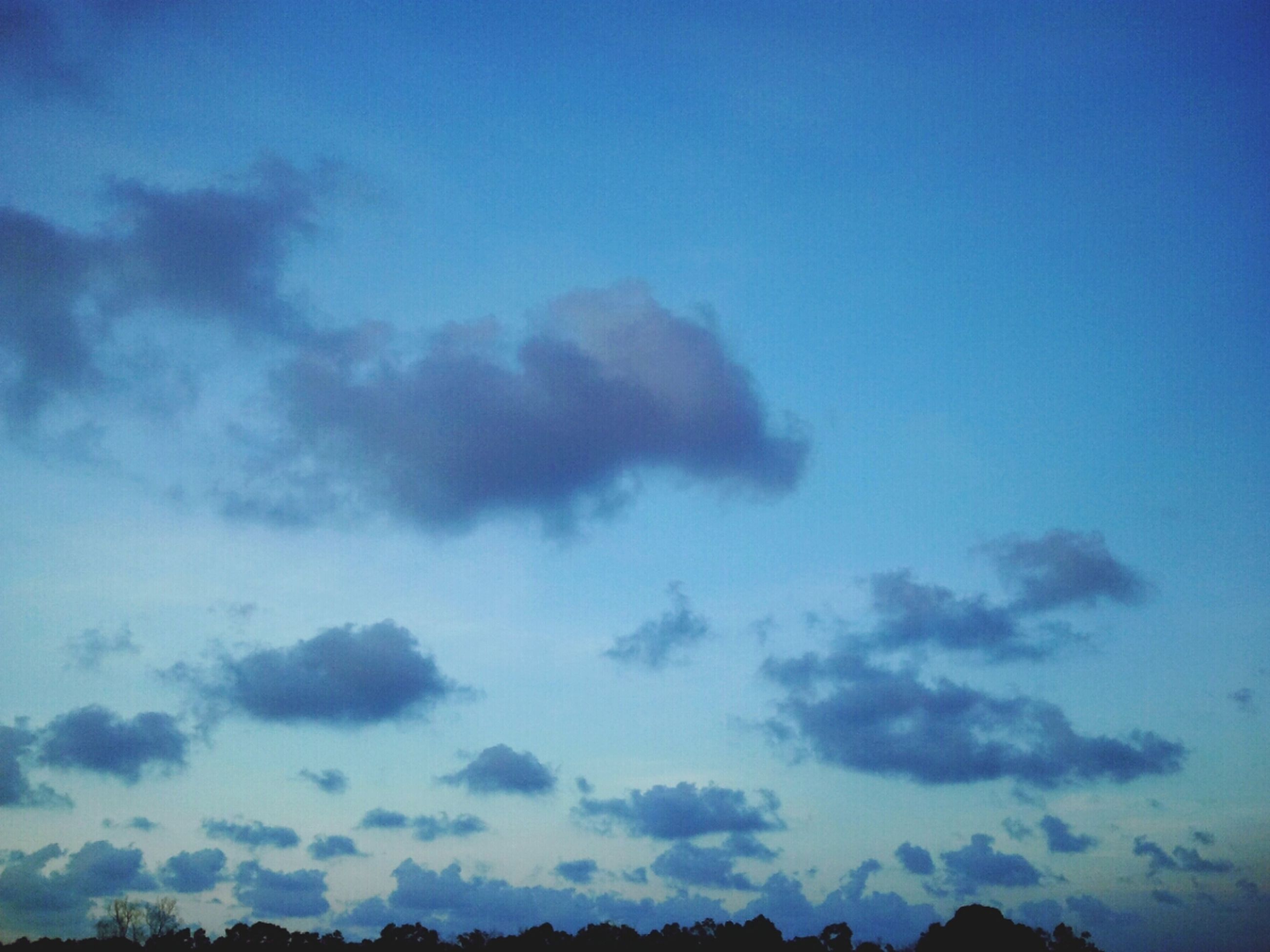sky, blue, scenics, tranquility, beauty in nature, tranquil scene, cloud - sky, low angle view, nature, silhouette, cloud, idyllic, cloudscape, copy space, outdoors, dusk, cloudy, no people, majestic, weather