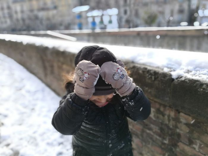 Girl Standing By Wall During Winter