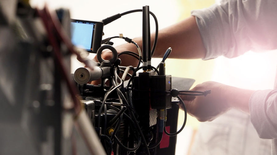 Cropped hands of photographer adjusting movie camera in studio