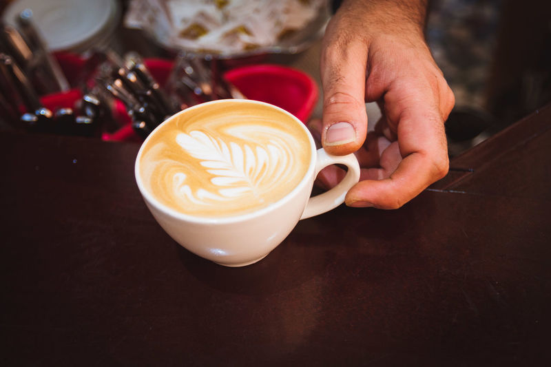 Cropped Hand Of Barista Holding Coffee Cup On Table At Cafe