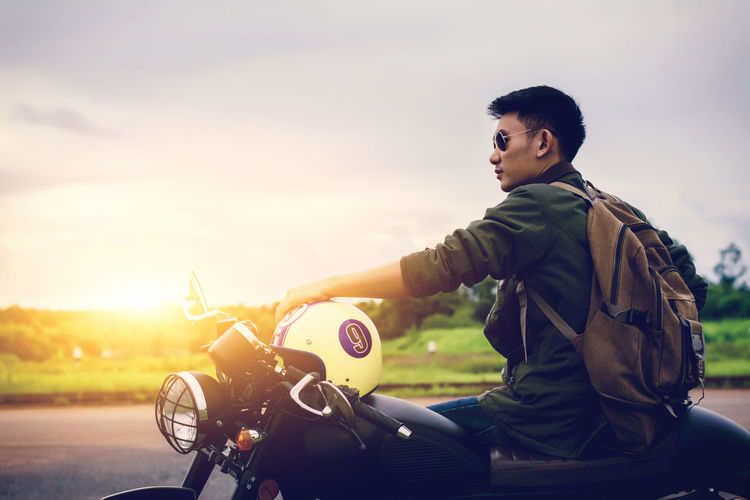Man sitting on motorcycle against sky