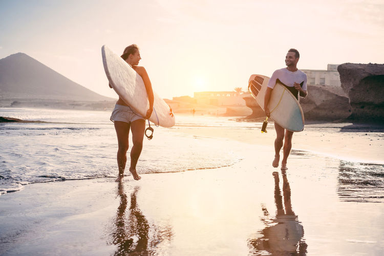 A couple is turning back after a surfing day Fun Happiness Laughing Surf Surfer Beach Day Extreme Sports Happiness Lifestyles Nature Outdoors People Sand Sea Sky Sport Sunlight Sunset Surfboard Togetherness Vacations Walking Water Young Adult