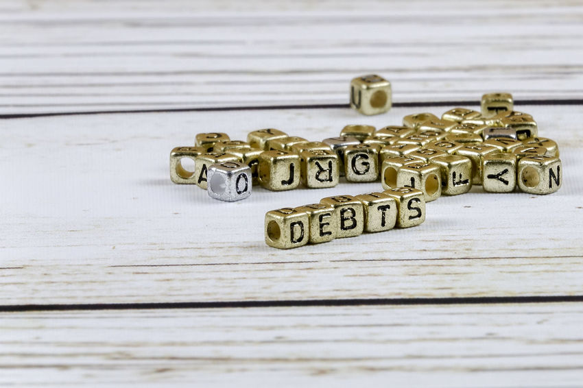 DEBT CONCEPT WITH GOLD DICE ON A WOODEN TABLE Capital Letter Close-up Communication Credit Card Debt Crisis Gold Colored High Angle View Indoors  Key Metal No People Number Old Selective Focus Single Word Still Life Table Text Toy Western Script Wood - Material