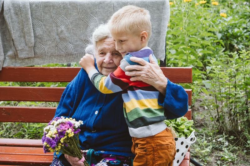 Grandmother and grandson embracing while sitting at park