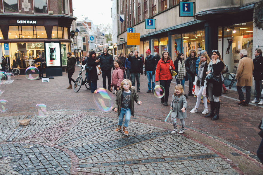 Architecture Baloons Bubbles Building Exterior Built Structure Children City Day Happiness Large Group Of People Leisure Activity Lifestyles Men Outdoors People Playing Real People Soap Bubbles Women Enjoy The New Normal