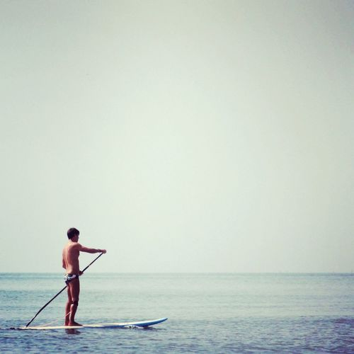 Full length of man paddle boarding in sea