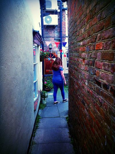 Rear veiw of girl walking down a alley to her home Architecture Rear View Women Brick Wall Full Length Real People Lifestyles One Person Building Exterior The Way Forward Outdoors Day Causal Clothing Moving On University Bunting Air Conditioning