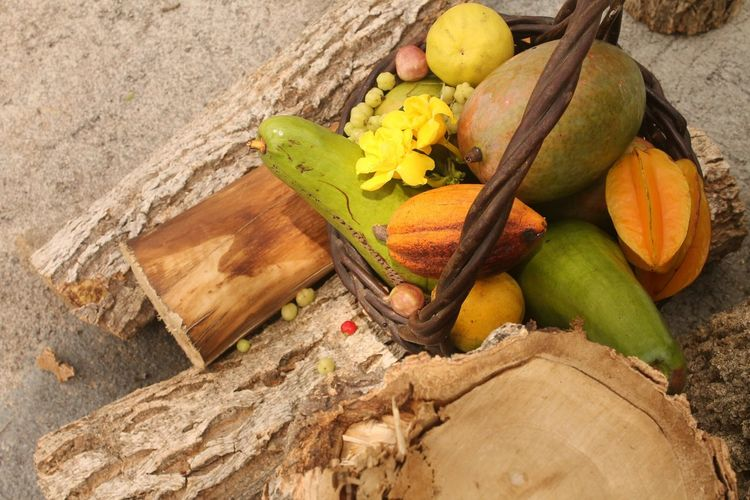 High Angle View Of Fruit And Vegetables In Basket On Logs