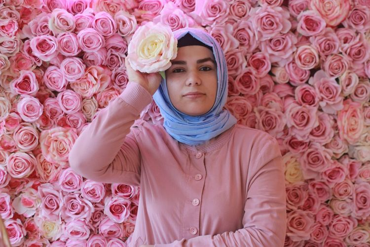 Portrait of young woman wearing hijab while standing against roses