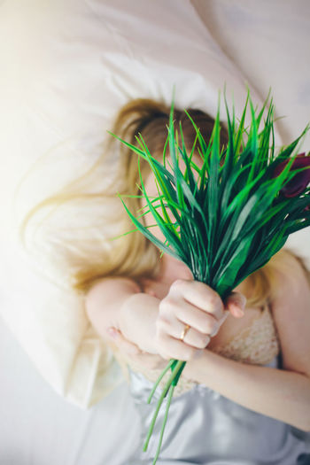 Girl with flowers on bed in the morning One Person Real People Holding Green Color Women Child Indoors  Lying Down Lifestyles Bed Childhood Furniture High Angle View Front View Plant Human Body Part Leisure Activity Relaxation Adult Hand Innocence Bed Bedroom Girl Morning Morning Light Flower Woman The Portraitist - 2019 EyeEm Awards