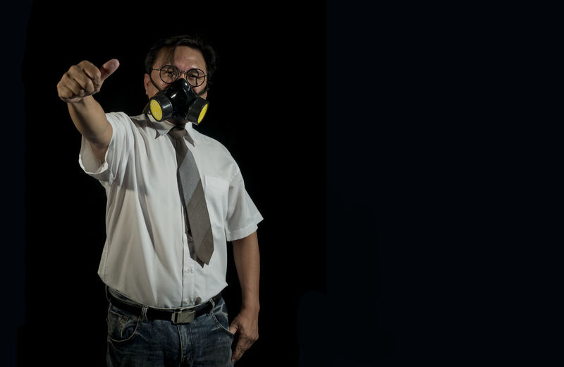 Portrait of businessmen wearing gas masks with a black background. Concept of pollution world Aggression  Business Concepts Chemical Dangerousdrivertobe Gas-mask Toxic Tragedy Uncertainty  Unhygienic Unpleasant Smell Warming Copy Space Disaster Safety