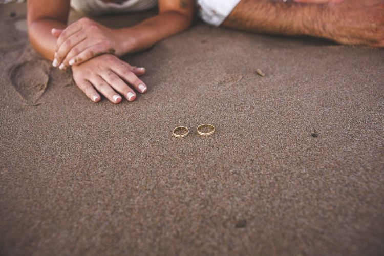 Cropped image of couple with rings on sand at beach