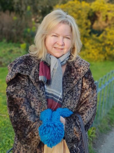 Portrait Of Smiling Woman In Winter Coat Standing Against Field