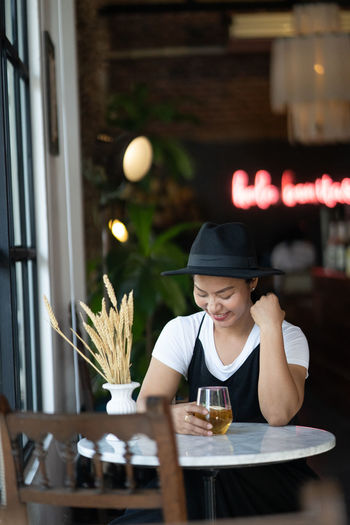 Midsection of woman holding drink in restaurant