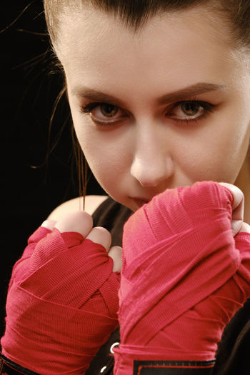 Close-up portrait of female boxer against black background
