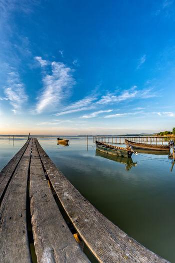 Pier over river against blue sky