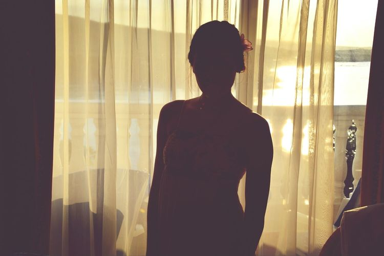 Woman standing by curtain in room