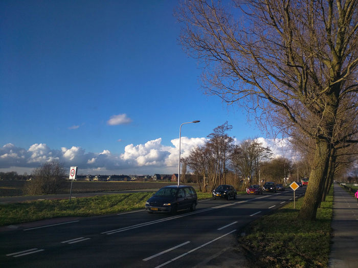 Cars on road against clear blue sky in city