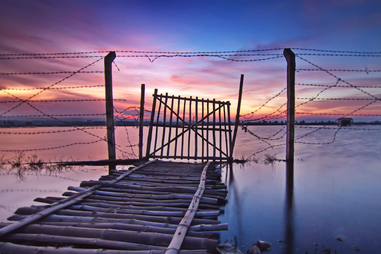 Broken fence on boardwalk by lake during sunset