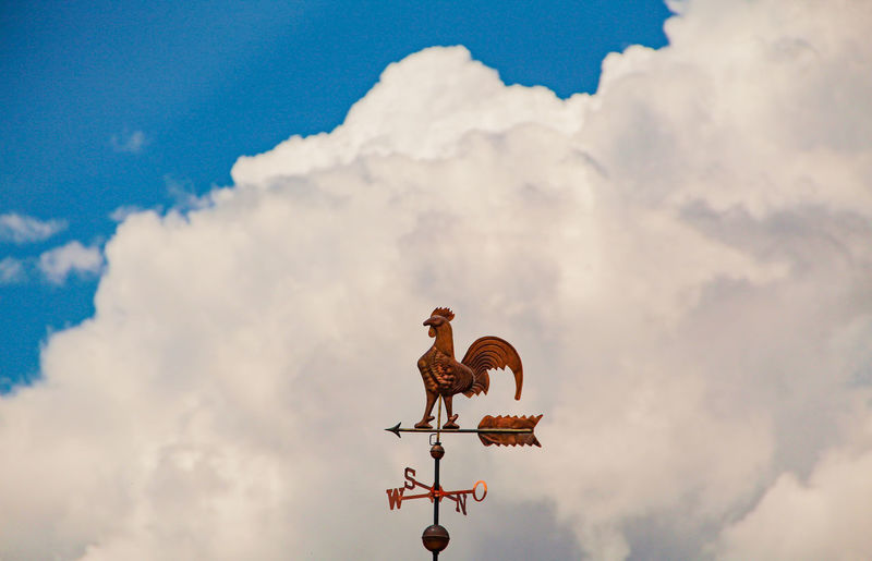 Weather vane against cloudy sky
