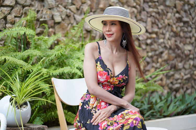 Young woman wearing hat sitting outdoors